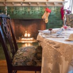 Dining room breakfast setting by fireplace with holiday decor