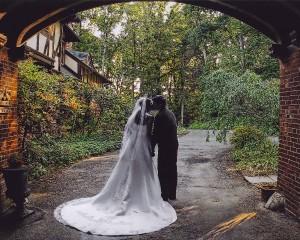 Bride and Groom Kissing Under Porte Coche