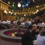 Carriage House courtyard dining with lights and lanterns