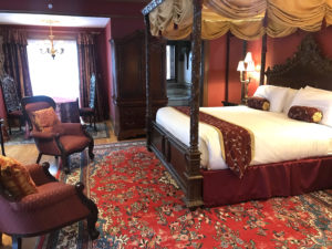 Romantic overnight guest room with red carpets, burgundy bed furnishings, fabric chairs and a king-size bed.