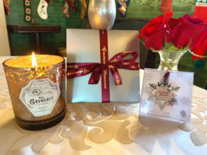 A lit candle in a brown glass holder, a gift certificate with red ribbon and gold lettering and a silver snowflake ornament sit in front of red roses on a table.